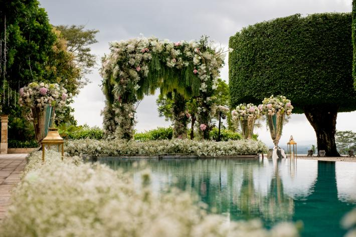 Poolside luxuy wedding floral arbor of white roses photographed by Morgan Lynn Razi