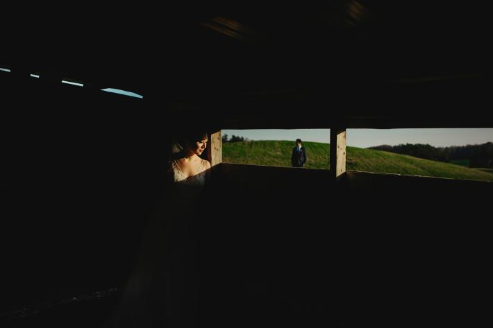 featured-bride-in-dramatic-afternoon-light-through-window-with-groom-in-field-in-background-worlds-best-wedding-photos-fer-juaristi
