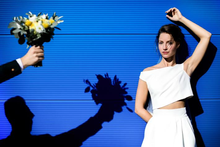 Shadow of bouquet being given to bride modern two piece gown - photo by Julien Laurent Georges