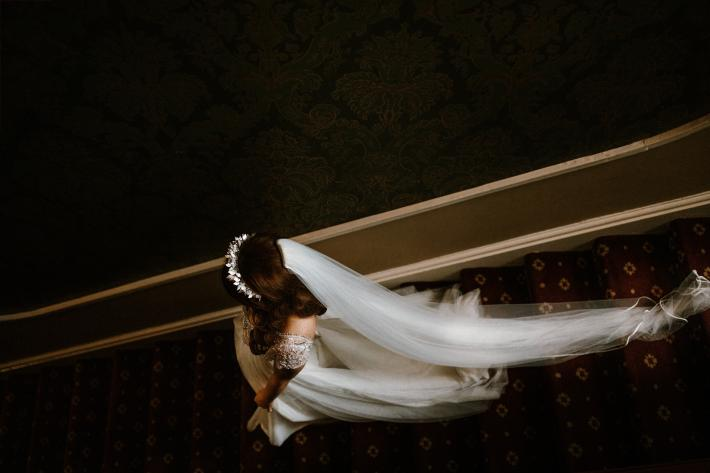 bride-descending-stairs-with-tiara-and-long-veil-white-cat-studio