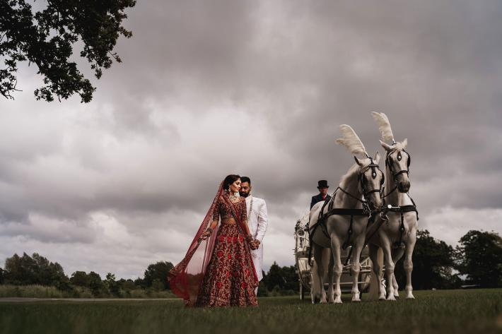 Elegant Indian wedding couple with decorated white horses - photographed by Rahul Khona of F5 in London