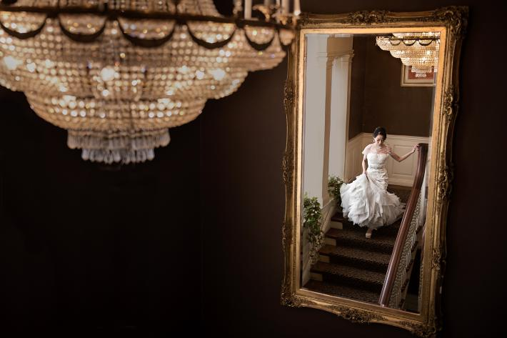 Bride reflected in gold-leaf mirror on elegant stairway - photo by David and Sherry - top Canadian photographers