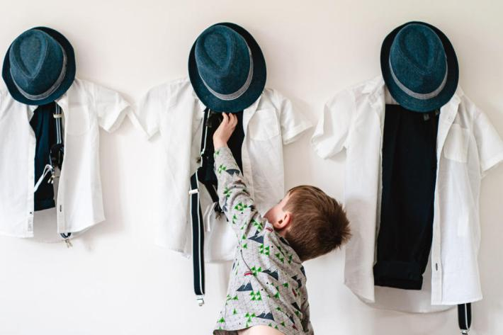 Little boy reaches for his wedding clothes and blue felt hat - photo by Andrew Billington - England