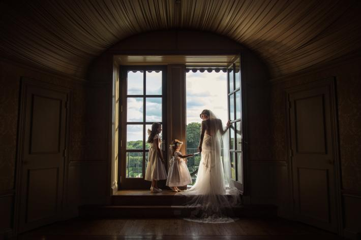 Flower girls in lace dresses with bride at window - photo by Cliff Mautner - PA