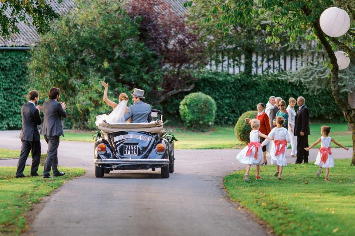 Just married couple leaves wedding in blue VW bug - photo by Sylvain Bouzat - France