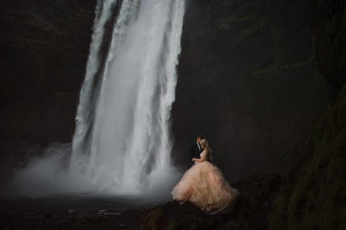 Bride in pink tulle ballgown with groom at bottom of waterfall - photo by Gabe McClintock - Alberta, Canada