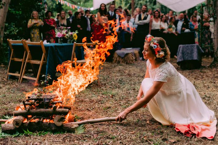 Bride wearing lace dress and floral crown stoking campfire - photo by Rich Howman - England