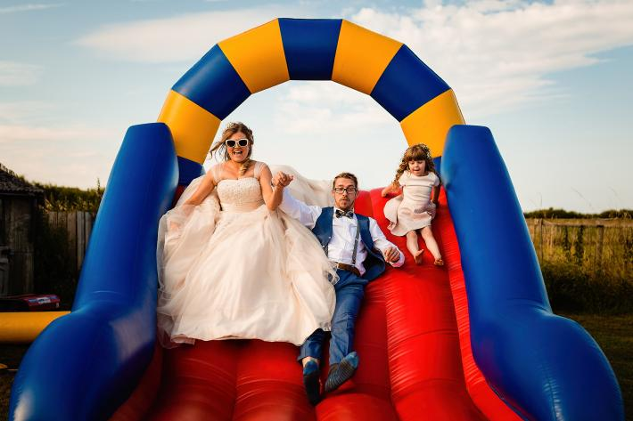 Bride, groom and little girl on blow-up slide, photo by Emma plus Rich, UK photographers  wedding photographers