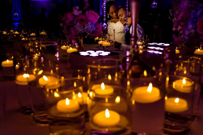 Portrait of bride and groom at table through candlelight - photo by Jide Alakija - NYC, New York