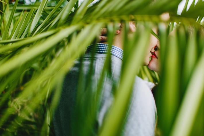 Couple sneaks a kiss behind ferns - photo by Ruan Redelinghuys