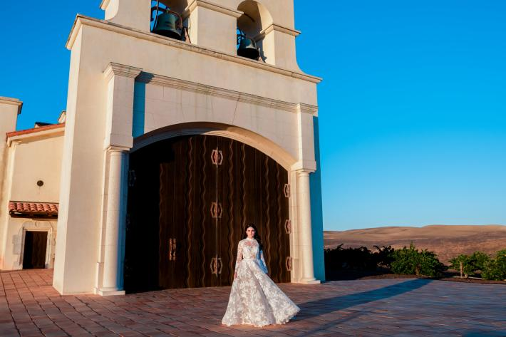 Bride-wearing-dramatic-lace-long-sleeve-gown-in-front-of-church-johnandjoseph-los-angeles