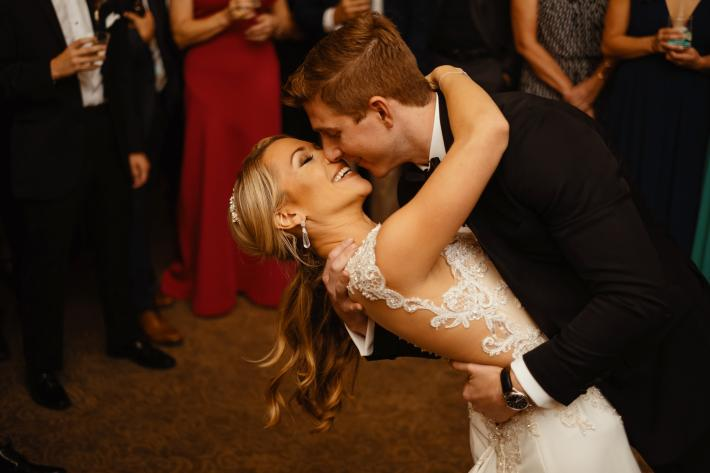 groom-dipping-bride-and-going-in-for-a-kiss-during-their-dance-photo-by-dark-roux
