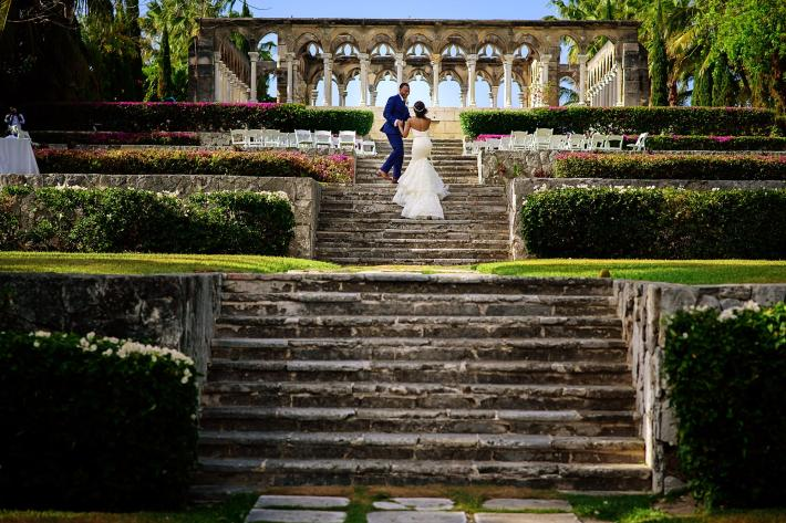 couple-ascend-stairs-to-greek-column-ceremony-bride-with-trumpet-lace-dress-worlds-best-wedding-photos-jide-alakija-new-york