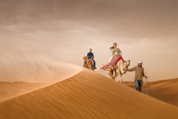 epic-bride-and-groom-portrait-on-camels-on-dunes-eye-jogia-photography