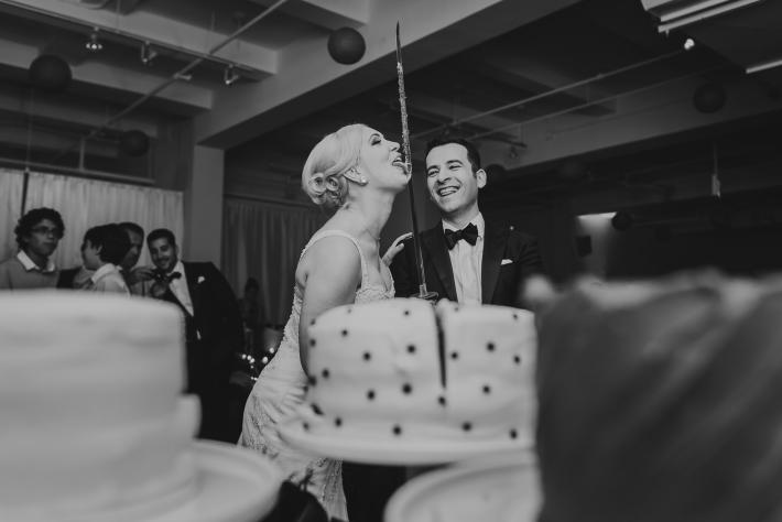 Bride licks frosting from sword used for cake cutting - photo by The Brenizers - New York