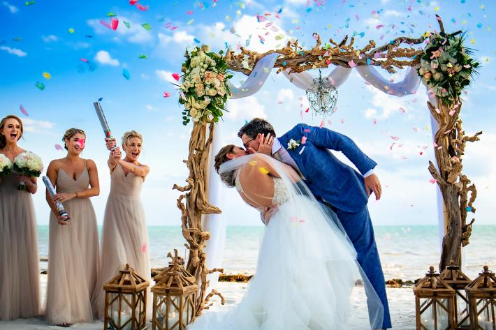 Bride and groom kiss at ceremony against blue sky and confetti by Michael Freas, North Carolina