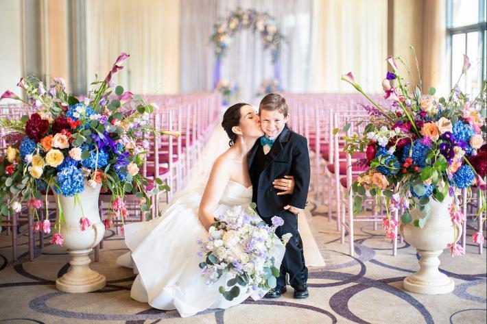 Bride kissing ring bearer on aisle runner among flowers - photo by Anna Schmidt DC