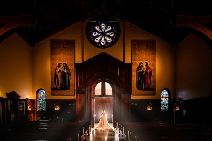 Bride standing in church entrance with light flooding in around her - photo by M.Hart Photography - Los Angeles