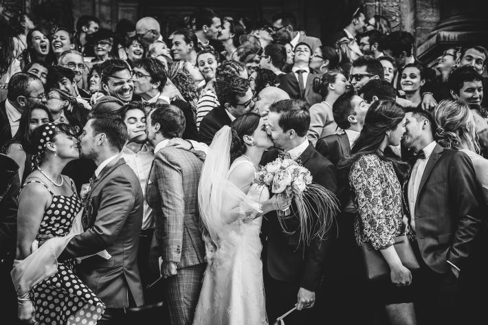 Couple kissing in a crowd of people kissing - photo by Julien Laurent-Georges - French wedding photographer