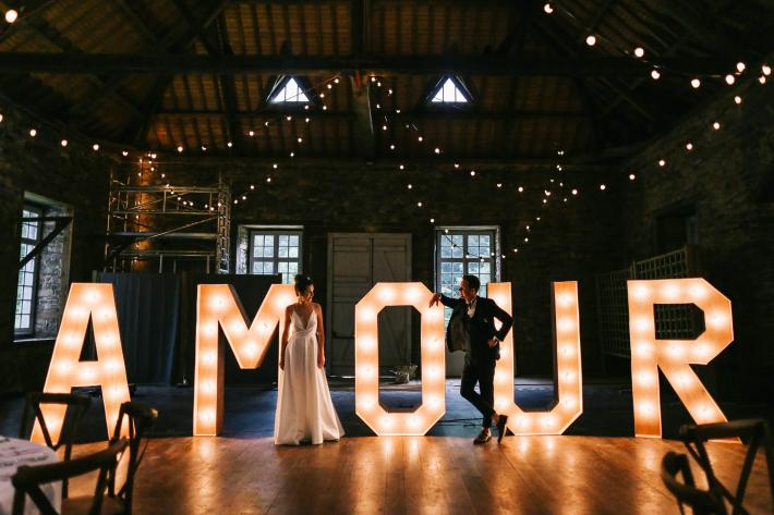 bride-and-groom-portrait-in-front-of-light-letters-amandine-ropars-france