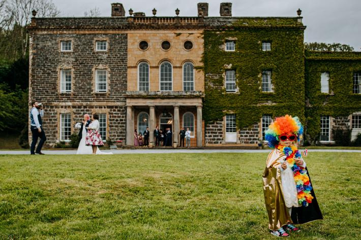 child-in-costume-as-guests-socialize-against-historic-building-m-and-g-wedding-photography