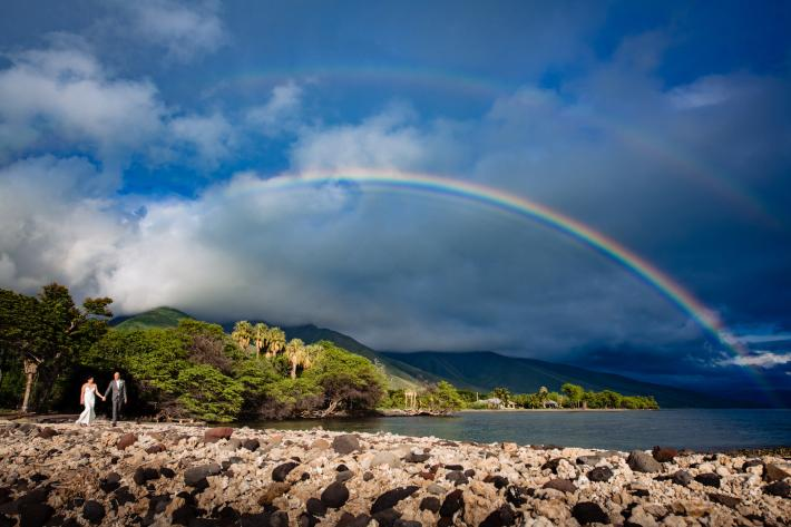 Bride and groom walking against double rainbow, Maui, Hawaii - photographed by Angela Nelson