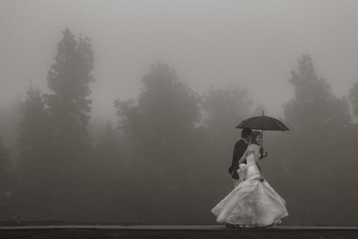Romantic photo of bride and groom walking in the fog and rain by Joel and Justyna, Ottawa wedding photographers